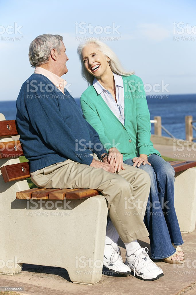 Senior Couple Sitting On Bench By Sea Together royalty-free stock photo