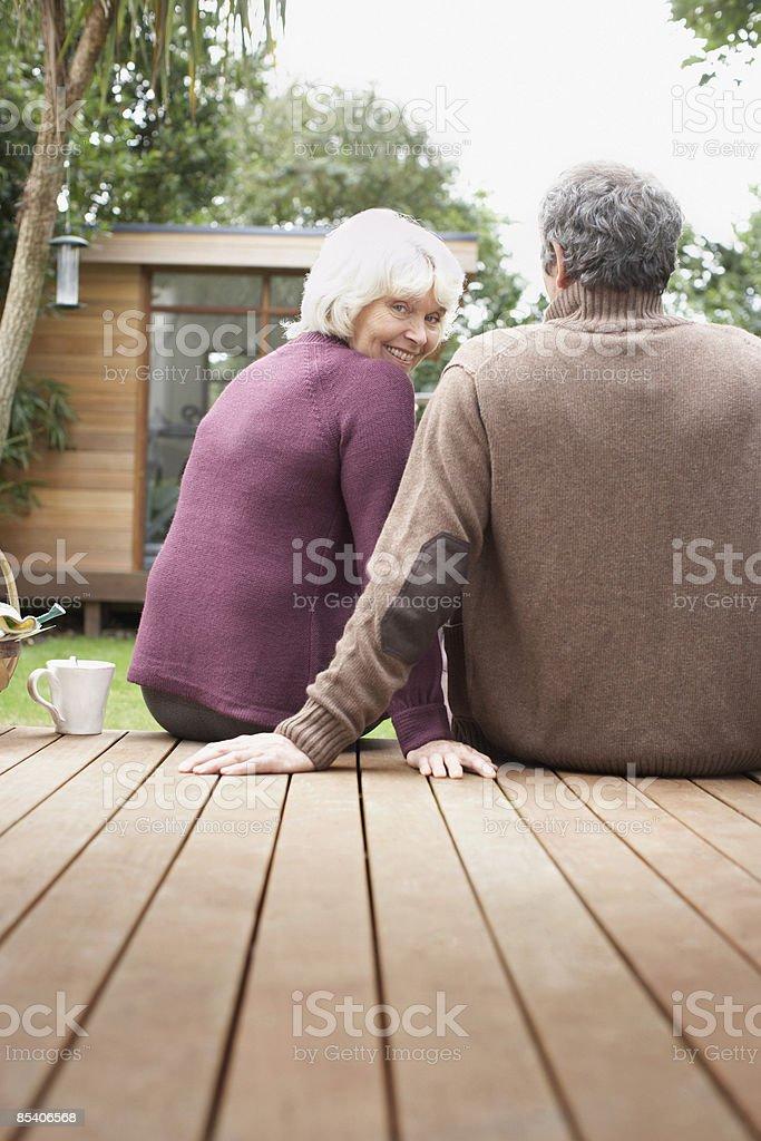 Senior couple sitting on deck in backyard royalty-free stock photo