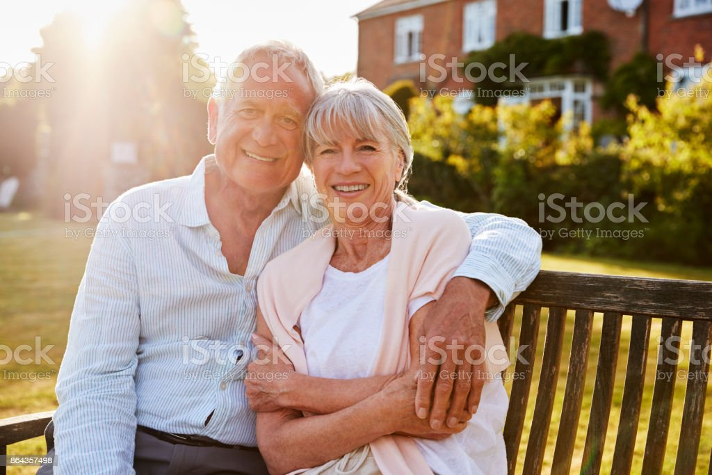 Senior Couple Sitting On Garden Bench In Evening Sunlight стоковое фото
