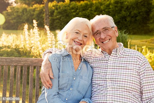 istock Senior Couple Sitting On Garden Bench In Evening Sunlight 874804766