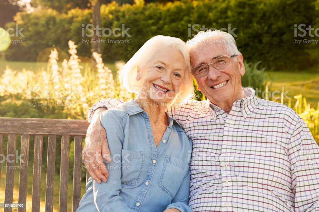 Senior Couple Sitting On Garden Bench In Evening Sunlight stock photo