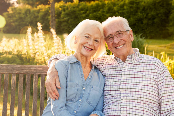 senior couple sitting on garden bench in evening sunlight - geriatrics stock pictures, royalty-free photos & images