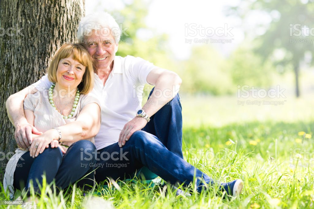 Senior couple sitting on grass стоковое фото