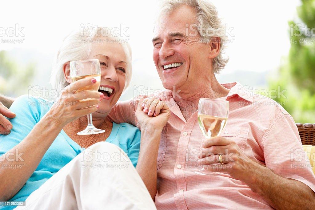 Sênior casal sentado bebendo vinho ao ar livre, no assento - foto de acervo