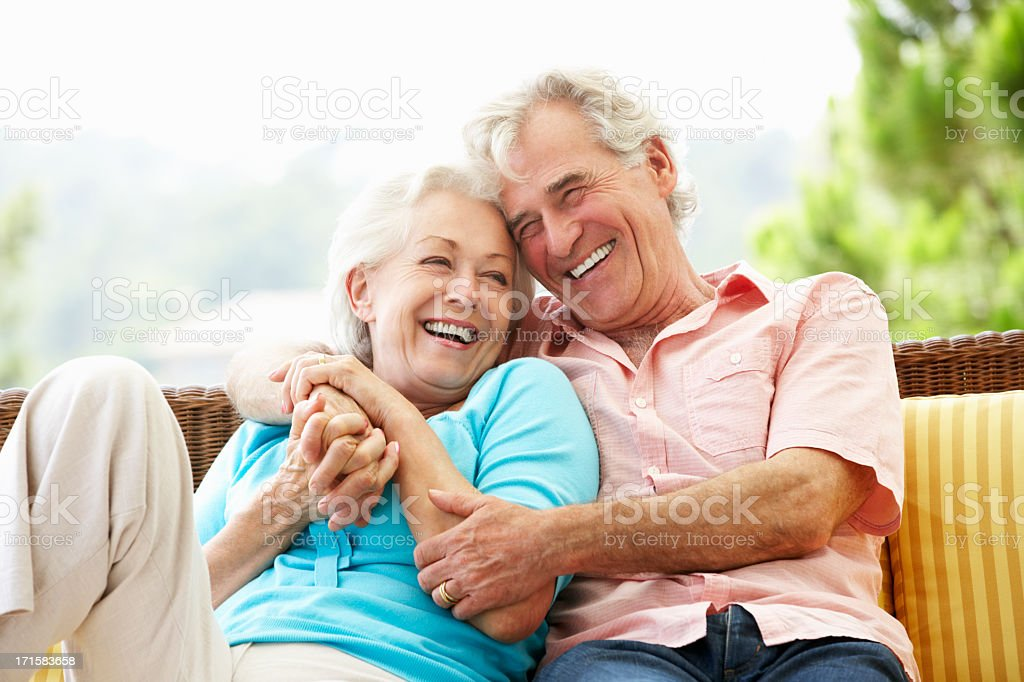 Senior Couple Sitting On Outdoor Seat Together stock photo