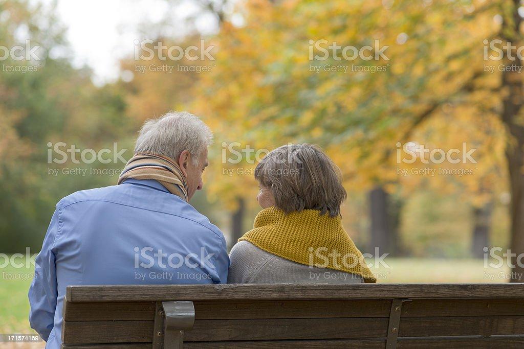 Senior couple sitting on park bench in autumn royalty-free stock photo