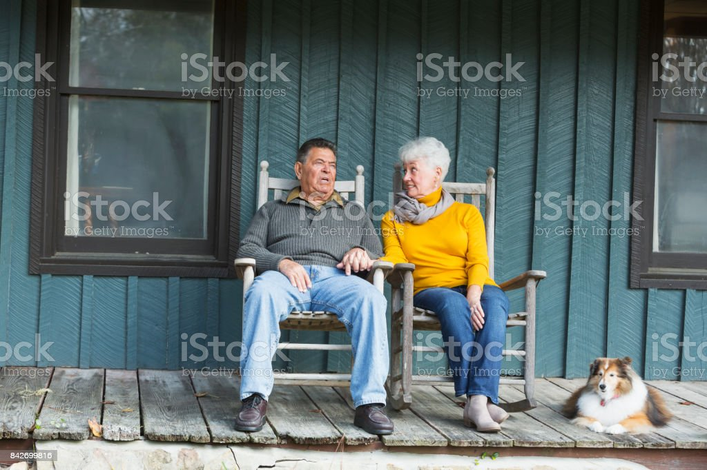 Senior couple sitting on porch, holding hands, with dog stock photo