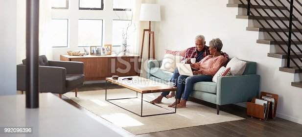 istock Senior Couple Sitting On Sofa At Home Using Laptop To Shop Online 992096396