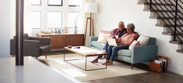 senior couple sitting on sofa at home using laptop to shop online - senior housing stock photos and pictures