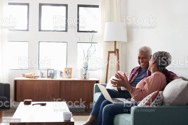 Senior couple sitting on sofa at home using laptop to shop online picture id992096494?b=1&k=6&m=992096494&s=612x612&h=c6bxz5nokp zf86xd8jqreuvvd6h0wqautxrrbsbnvm=