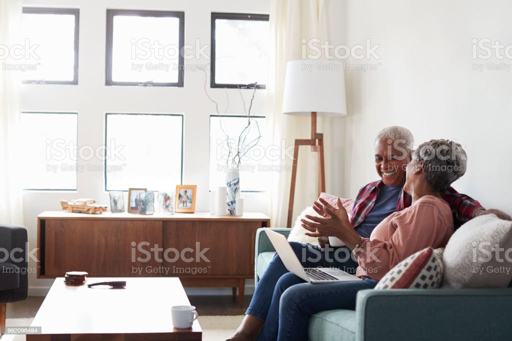 Senior Couple Sitting On Sofa At Home Using Laptop To Shop Online stock photo