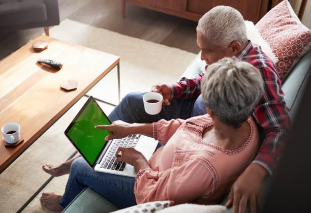 älteres paar auf sofa sitzen zu hause mit laptop shop online - sofabezüge stock-fotos und bilder