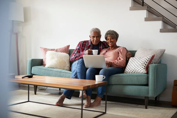 Senior Couple Sitting On Sofa At Home Using Laptop To Shop Online Senior Couple Sitting On Sofa At Home Using Laptop To Shop Online senior couple stock pictures, royalty-free photos & images