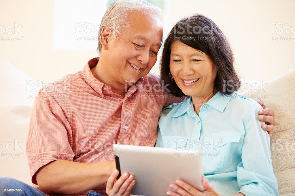 Senior Couple Sitting On Sofa Using Digital Tablet stock photo