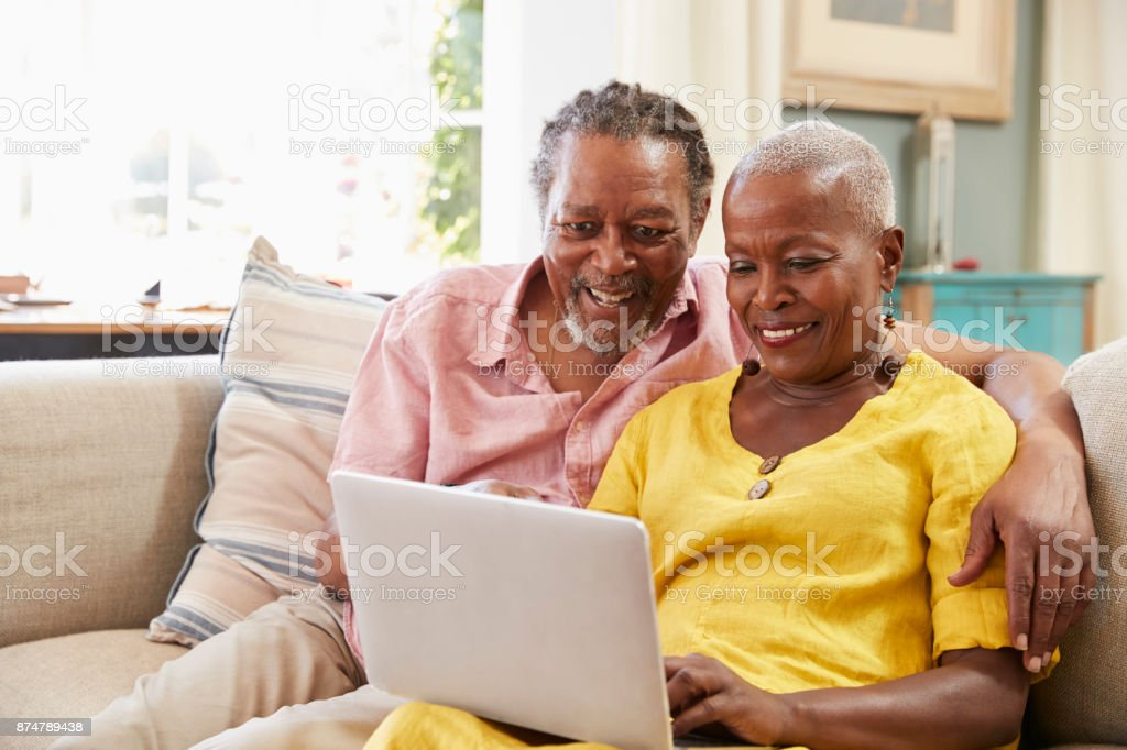 Senior Couple Sitting On Sofa Using Laptop At Home Together stock photo