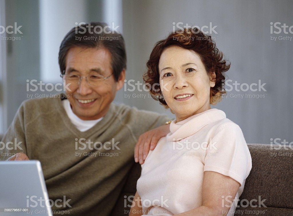 Senior couple sitting on sofa using laptop, portrait of woman royalty-free stock photo