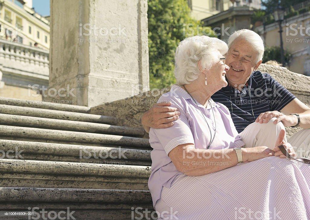 Senior couple sitting on steps, smiling photo libre de droits