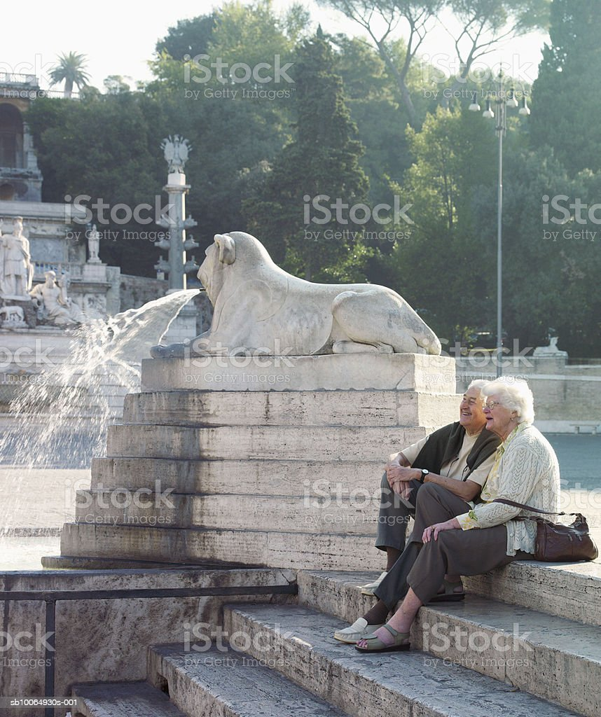 Senior couple sitting on steps, smiling royalty-free stock photo
