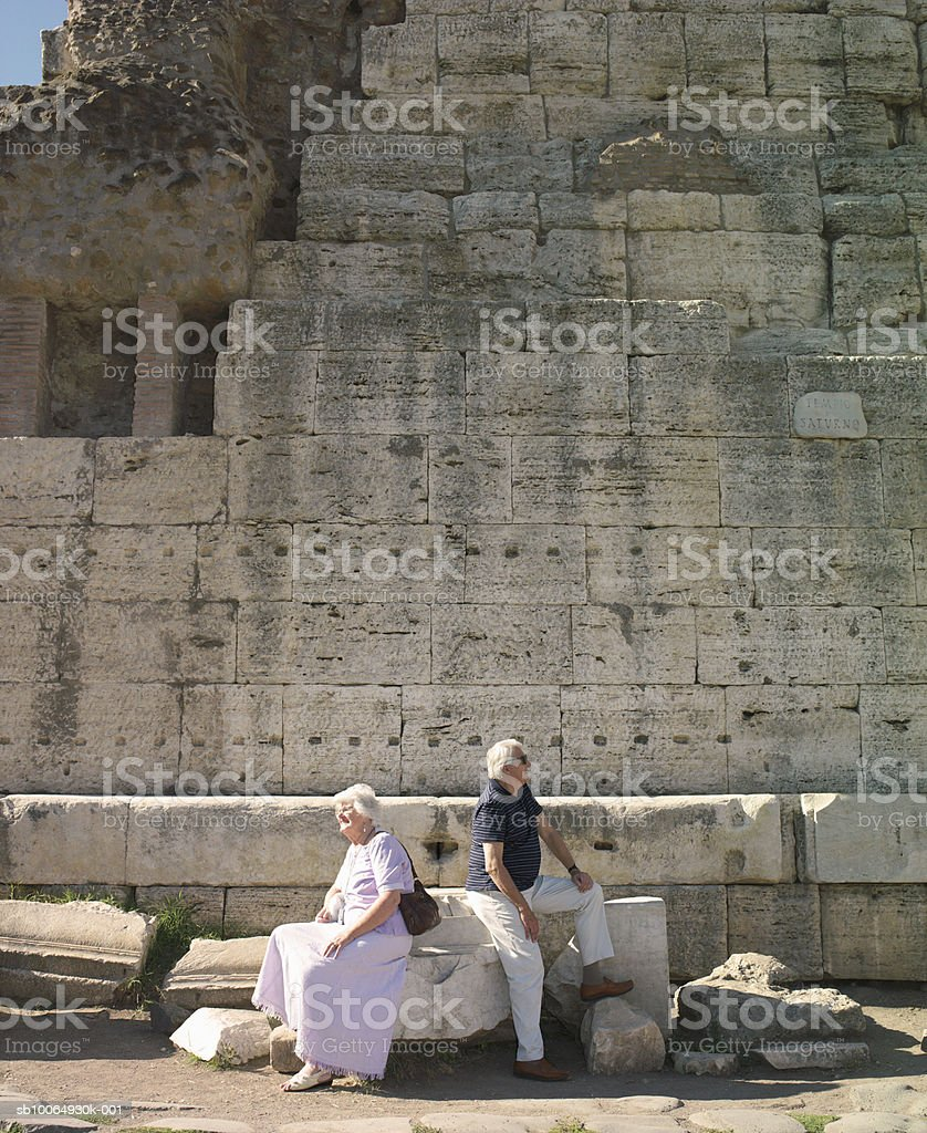 Senior couple sitting on stone at ancient site royalty-free 스톡 사진