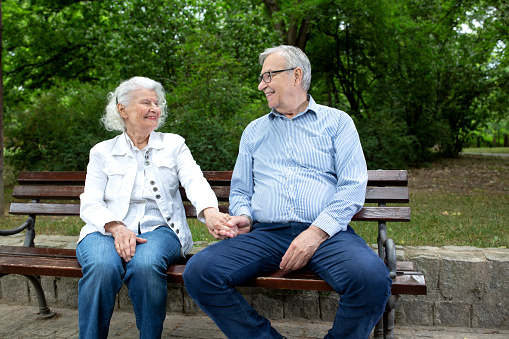 Senior couple sitting on the park bench and chatting