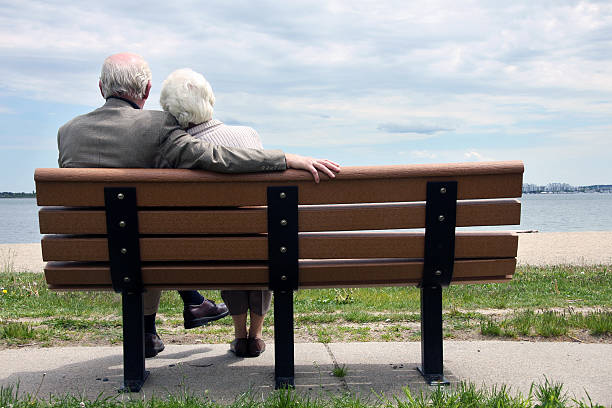 senior couple assis sur le banc - banc photos et images de collection