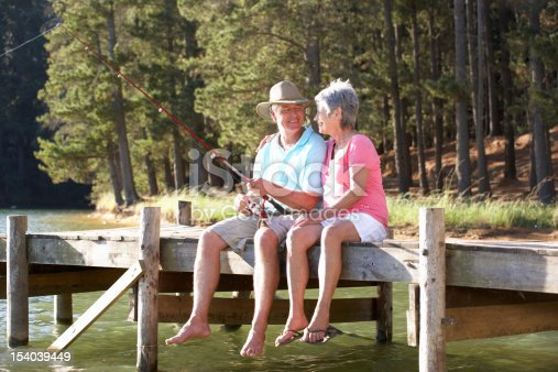 483319252 istock photo Senior couple sitting on wooden dock and fishing 154039449