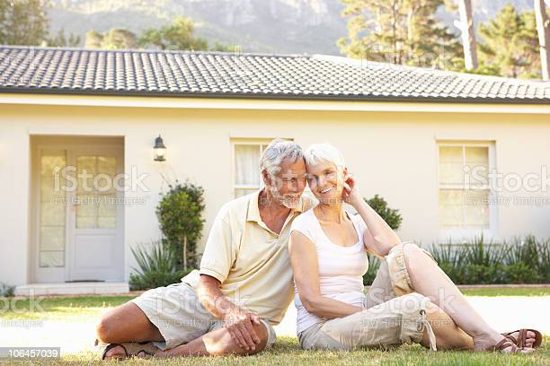 Senior Couple Sitting Outside Dream Home Stock Photo - Download Image Now