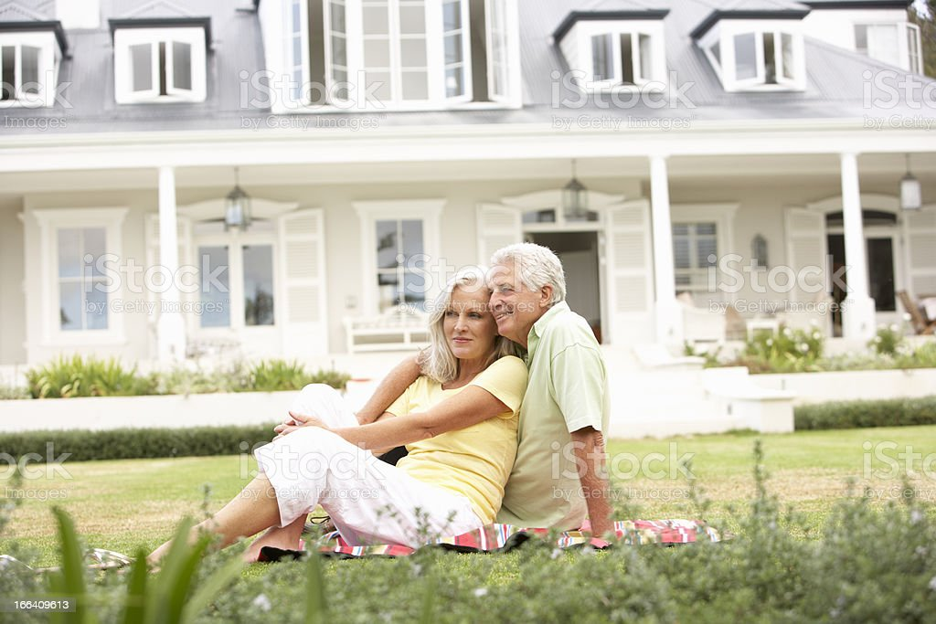 Senior Couple Sitting Outside On Lawn stock photo