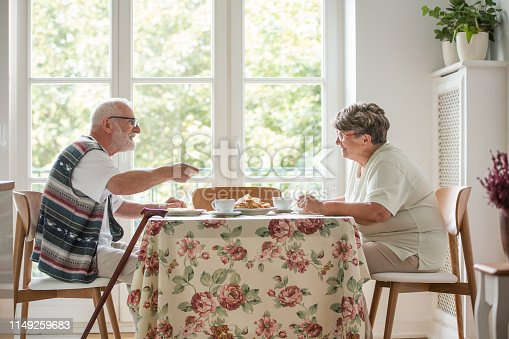 istock Senior couple sitting together at table drinking tea and eating cake 1149259683