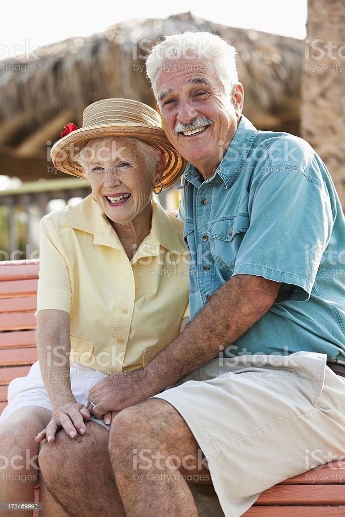 Senior couple sitting together on bench stock photo