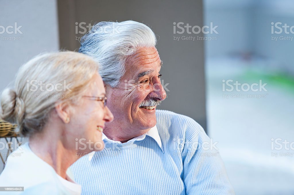 Senior couple sitting together on patio royalty-free stock photo