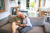 Elevated view of smiling Spanish seniors in their 60s sitting side by side on sofa and using digital tablet in family home.