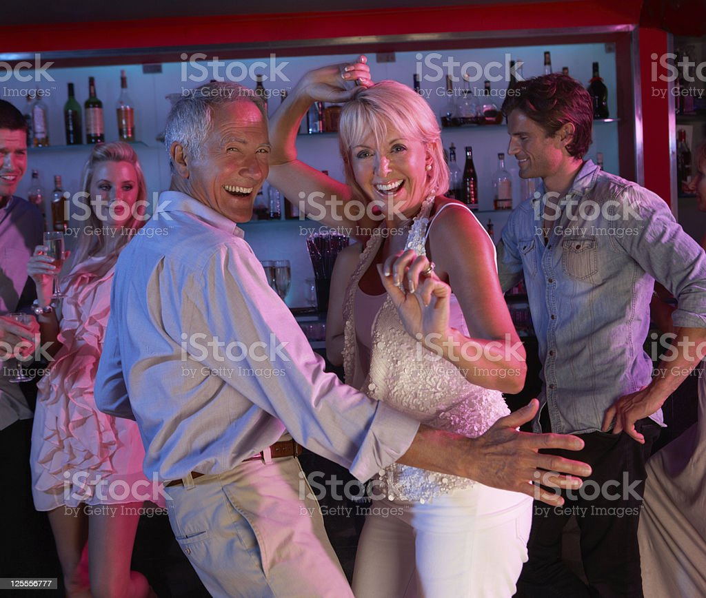 Senior couple smiling and dancing at a bar stock photo