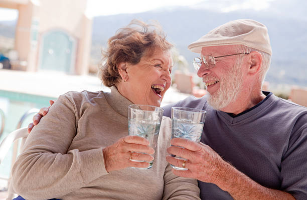 Senior couple smiling and having drinks stock photo