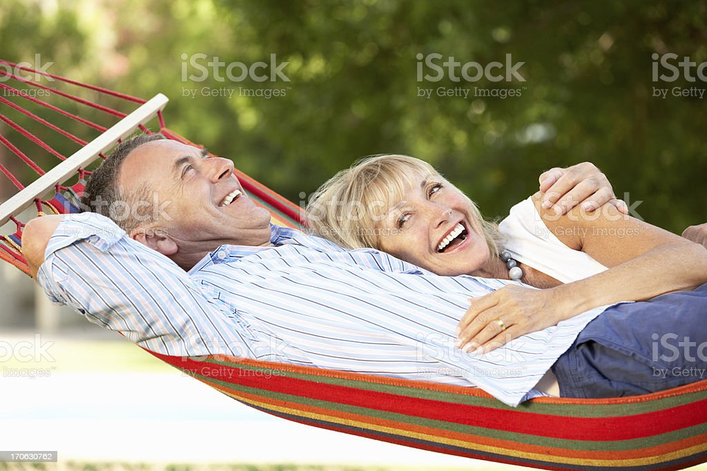 Senior couple smiling and relaxing in red striped hammock stock photo
