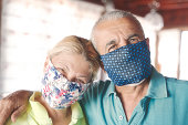istock Senior couple smiling behind the face mask protection of COVID-19 1261227145