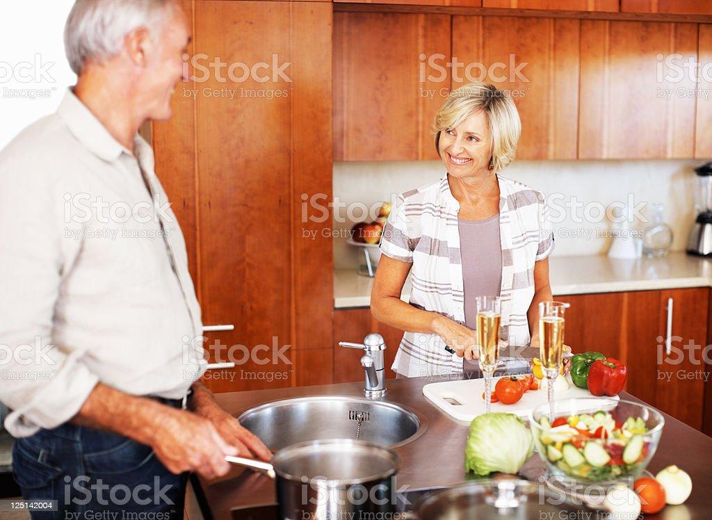 Senior couple smiling while cooking royalty-free stock photo