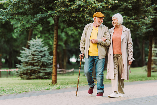 Senior couple smiling while walking on path in park