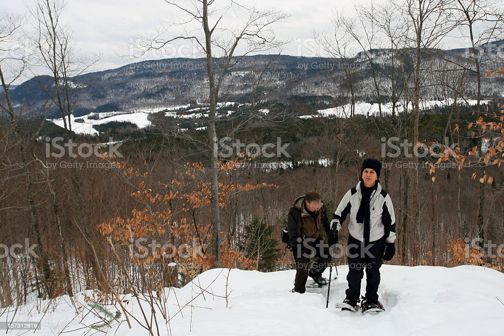 Senior Couple Snowshoeing in Winter Trail stock photo