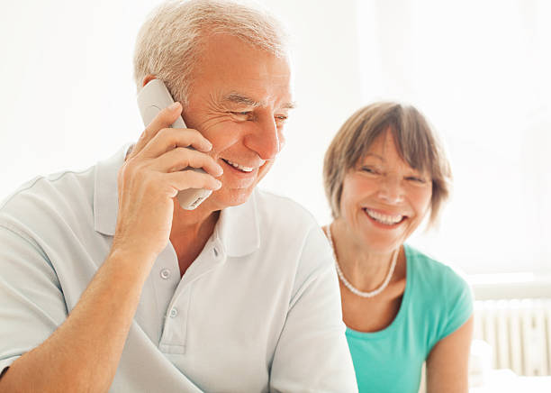 Senior couple speaking on the phone Senior couple speaking on the phone cordless phone stock pictures, royalty-free photos & images