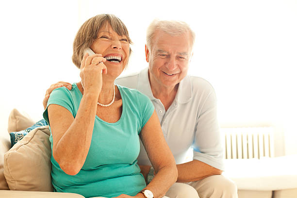 Senior couple speaking on the phone with their loved ones Senior couple speaking on the phone with their loved ones cordless phone stock pictures, royalty-free photos & images
