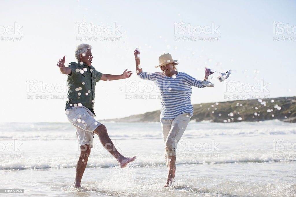 Senior couple splashing in ocean stock photo
