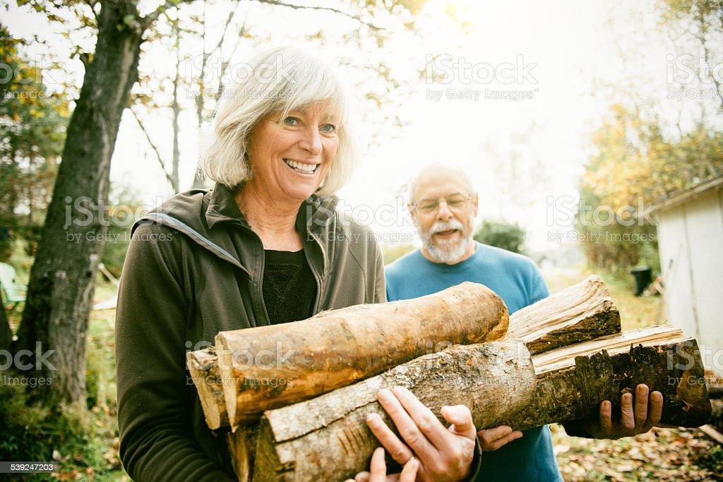 Altes Paar Stapeln Feuerholz auf den Garten – Foto