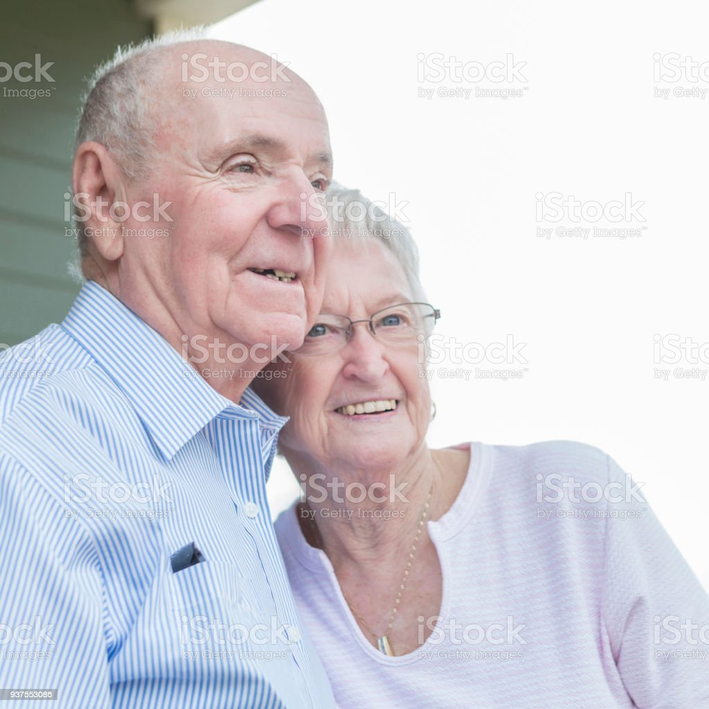 Senior couple stand together on front porch stock photo