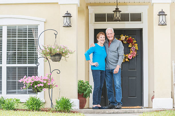 senior couple standing at front door of home - senior housing stock photos and pictures