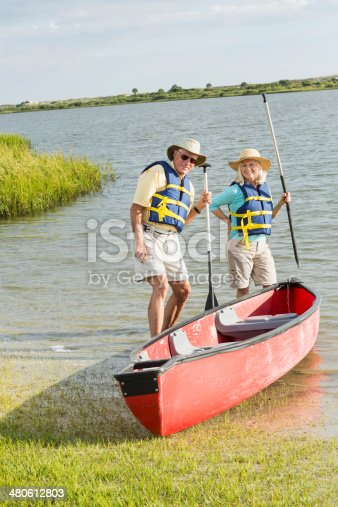 istock Senior couple standing beside canoe 480612803