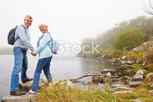 istock Senior couple standing by a lake, smiling to a camera 479288016