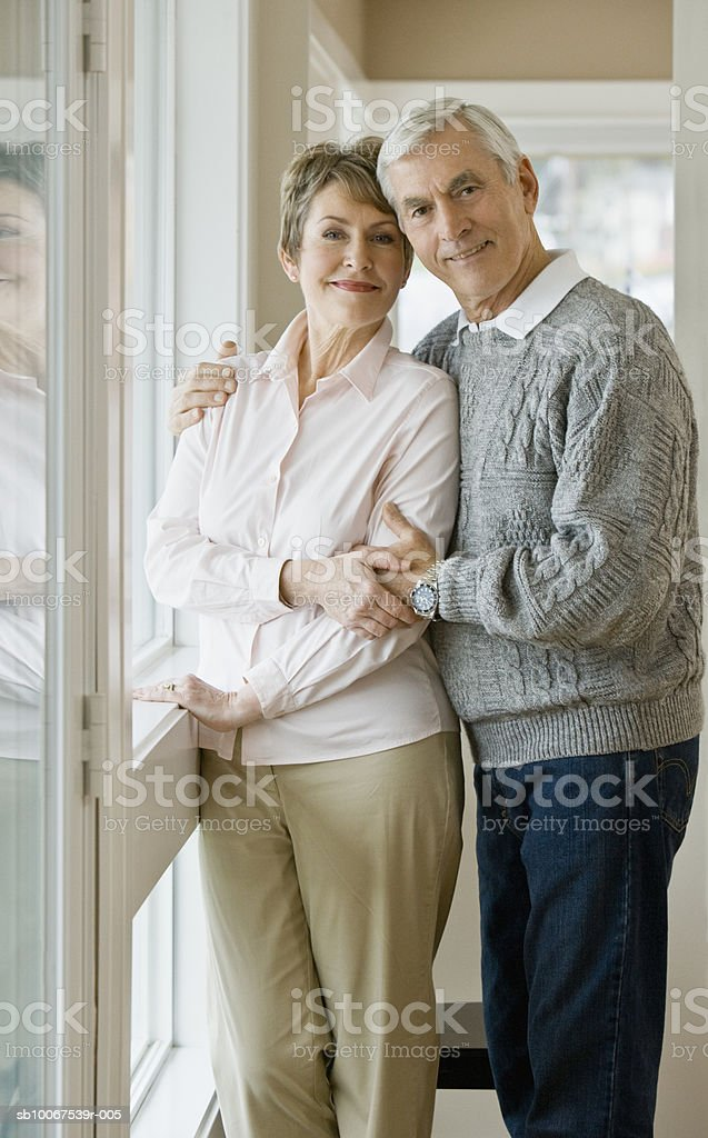 Senior couple standing by window, smiling, portrait 免版稅 stock photo