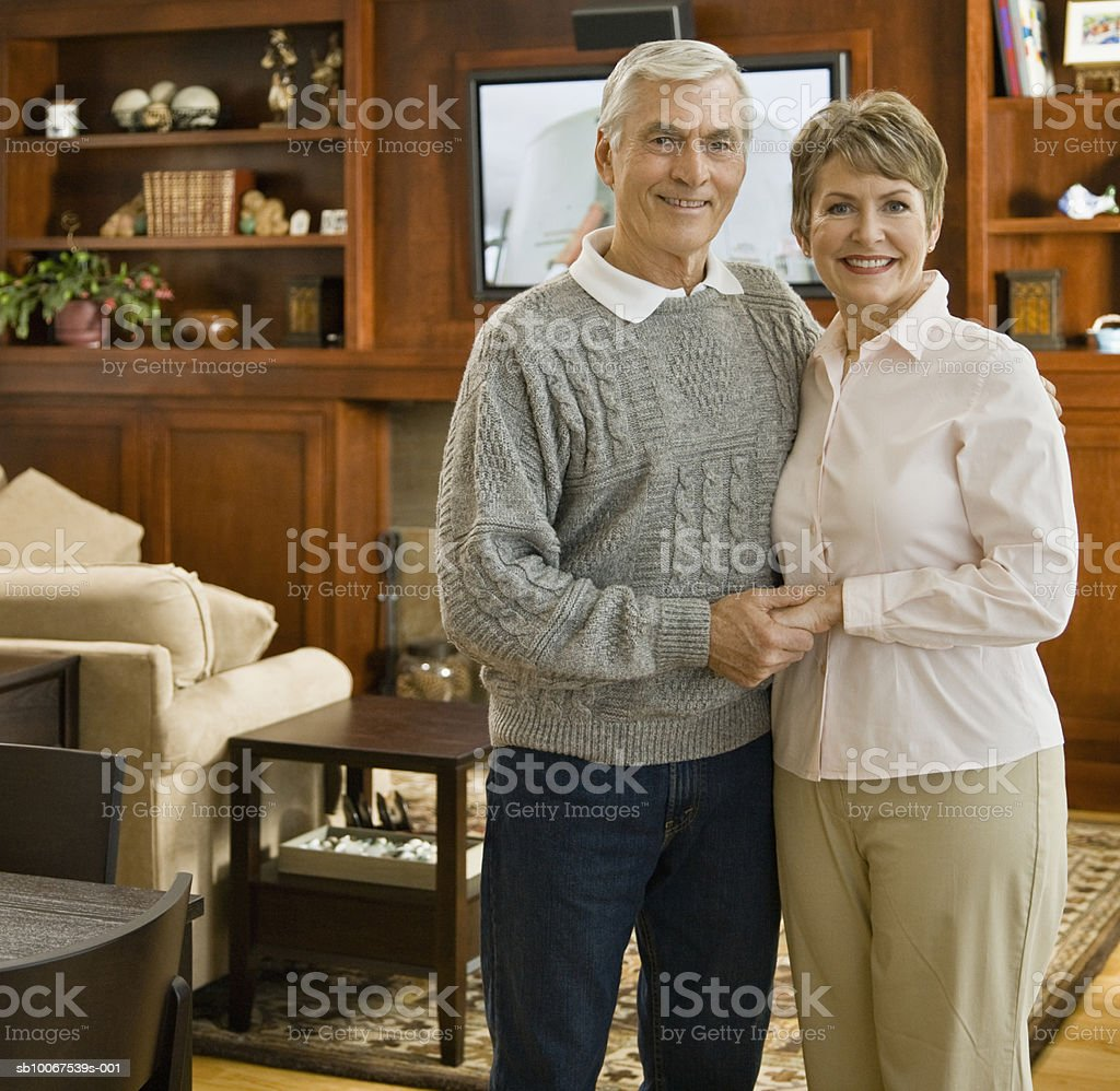 Senior couple standing in living room, smiling, portrait royalty-free stock photo
