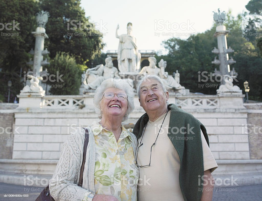 Senior couple standing in street, looking up, smiling 免版稅 stock photo